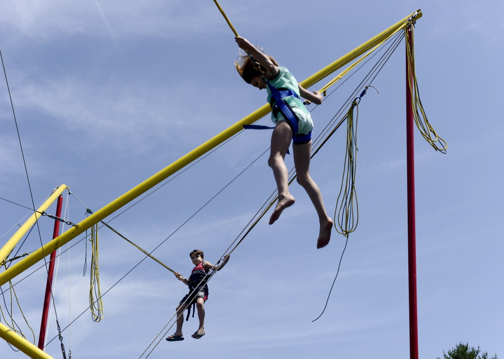 Holiday Adams, 11, and her brother Cash Adams, 8, jump on the trampoline at La Kermesse in Biddeford on Saturday. The 32nd annual Franco-American festival continues through Sunday at the Biddeford Intermediate School field on Hill Street.