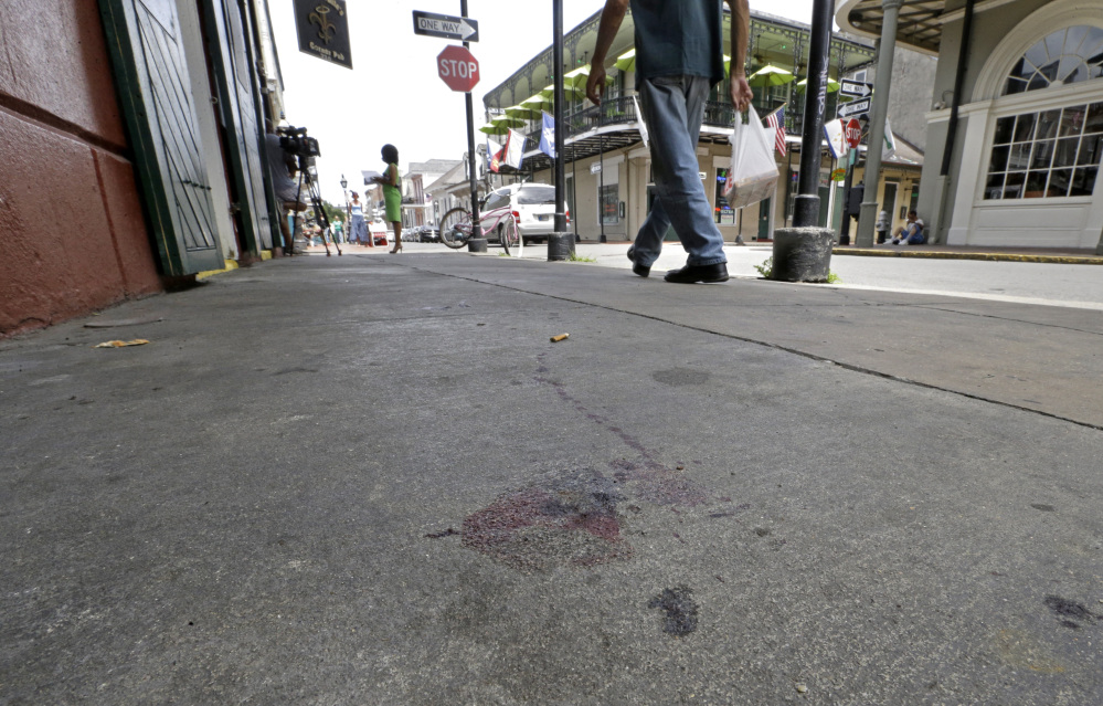 Blood stains are seen on the sidewalk at the scene of a shooting that happened early Sunday morning on Bourbon Street in New Orleans. Nine people were injured, one seriously, according to New Orleans Police.