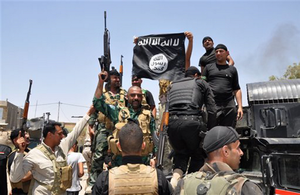 Iraqi security forces hold up a flag of the Islamic State in Iraq and the Levant they captured during an operation to regain control of Dallah Abbas north of Baqouba, the capital of Iraq's Diyala province, 35 miles northeast of Baghdad. The Islamic State, which already controls vast swaths in northern and eastern Syria amid the chaos of that nation's civil war, aims to erase the borders of the modern Middle East and impose its strict brand of Shariah law.