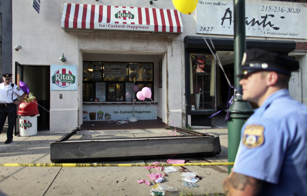 Investigators look over the debris of a fallen security door at a Rita's Water Ice store in Philadelphia on Saturday. The metal security grate detached, killing a 3-year-old girl.