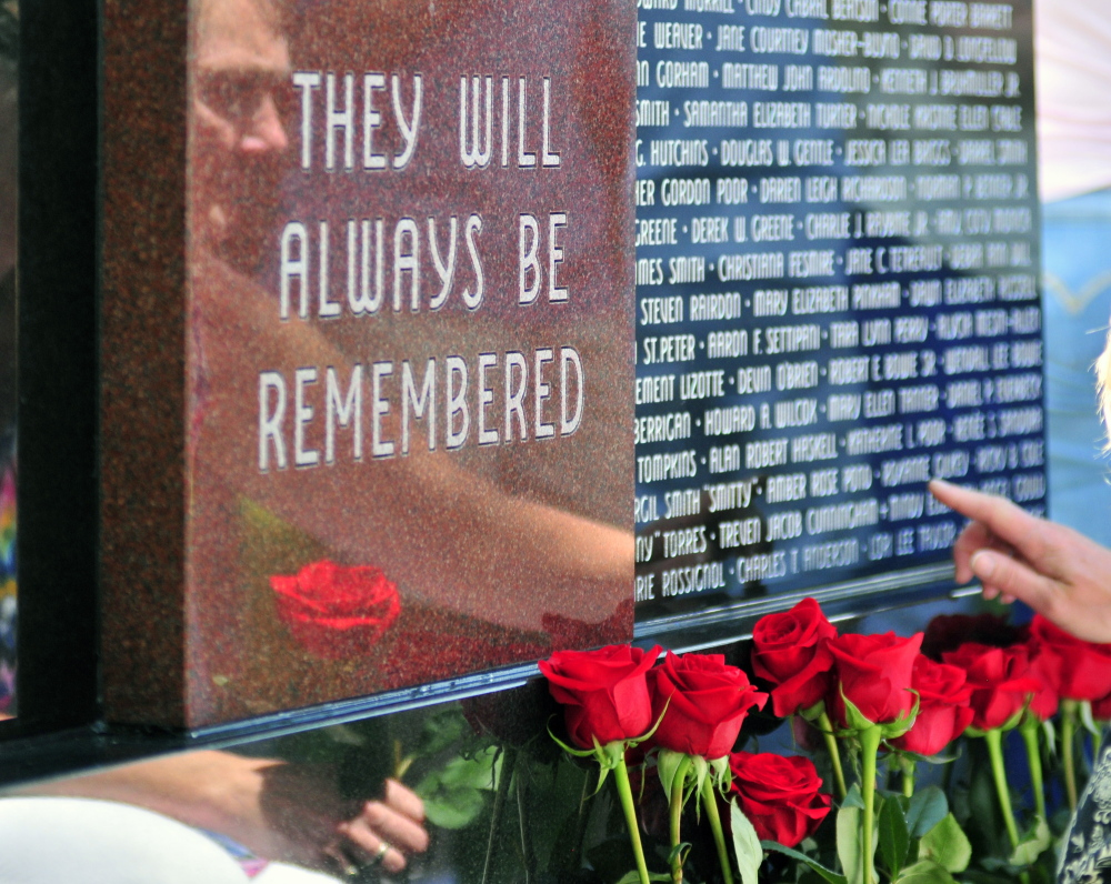 Survivors place roses in front of the Maine Murder Victims' Memorial Monument at the end of the dedication ceremony.