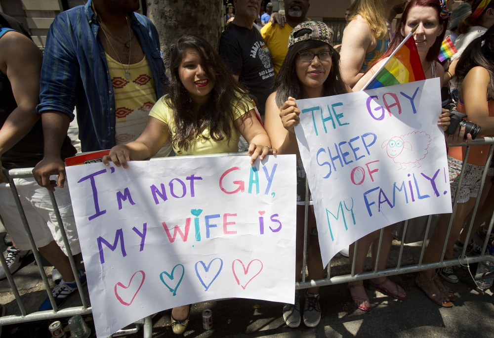 Spectators hold placards as they watch the annual Gay Pride Parade on Christopher Street in  Manhattan on Sunday.