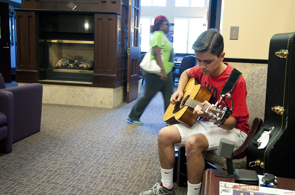 Nick Moniz, 17, of Naugatuck, Conn., plays guitar in the lobby of the Harold Leever Regional Cancer Center in Waterbury, Conn. Moniz played music as part of a community service project and liked it so much he is doing it during his free time in the summer.