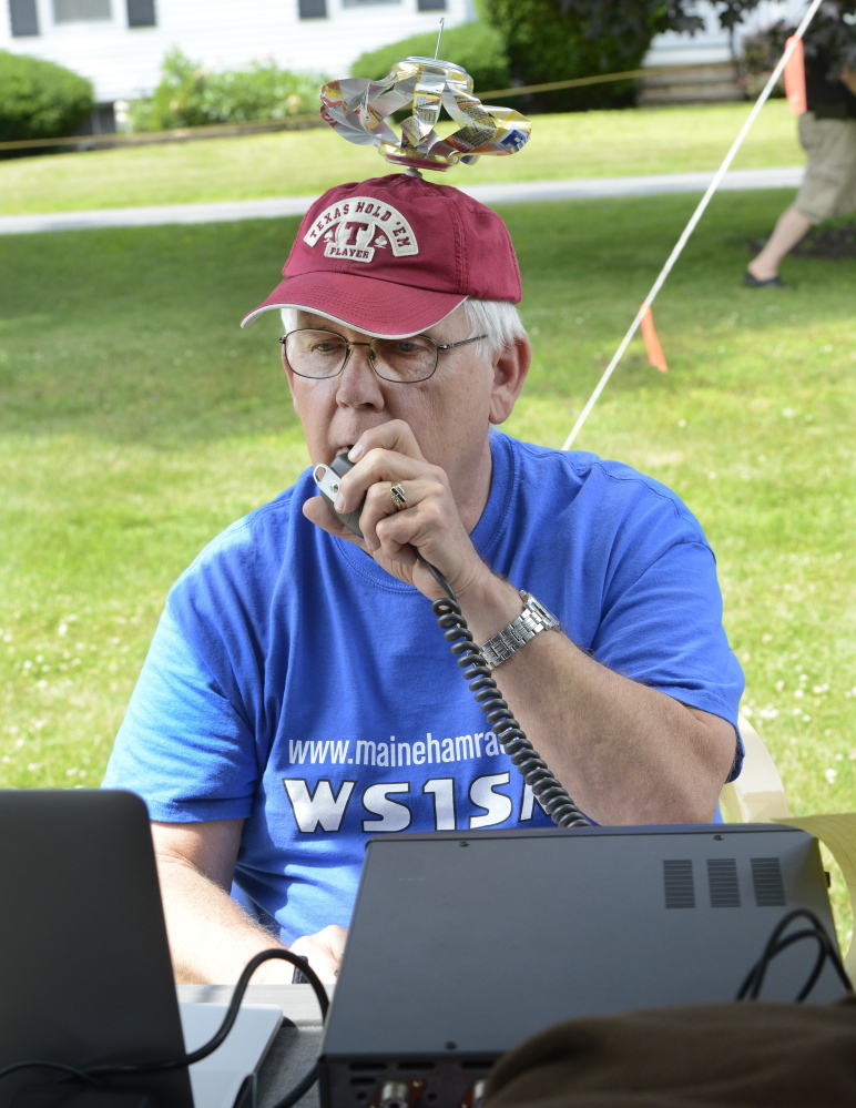 Frank Krizan of Garland, Texas, who spends his summers in Maine, makes a call during a local ham radio group event Saturday at a Scarborough campground.