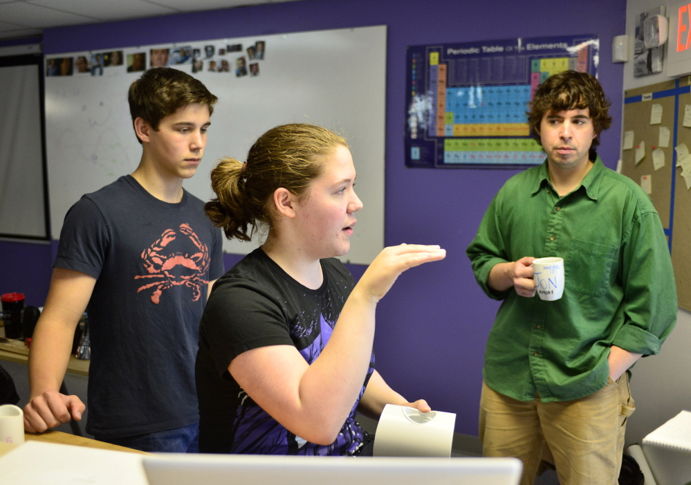 Baxter Academy student Erin Whitney talks about her team's engineering project this month as student Caedan Holdan, left, and engineering teacher Jonathan Amory listen. The students worked on their independent projects each Friday during the school year and then displayed their innovations.