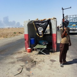 An al-Qaida-inspired militant stands guard recently at a checkpoint captured from the Iraqi Army outside Beiji refinery, some 155 miles north of Baghdad. The Sunni militant offensive has prompted Shiite militias to reconstitute themselves, deepening fears of a return to the sectarian bloodletting that pushed Iraq to the brink of civil war in 2006 and 2007.