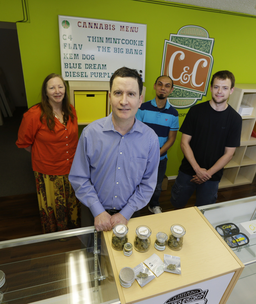 Pete O'Neil, second from left, stands in his soon-to-be-open medical marijuana dispensary in Seattle with three of his employees in the background.