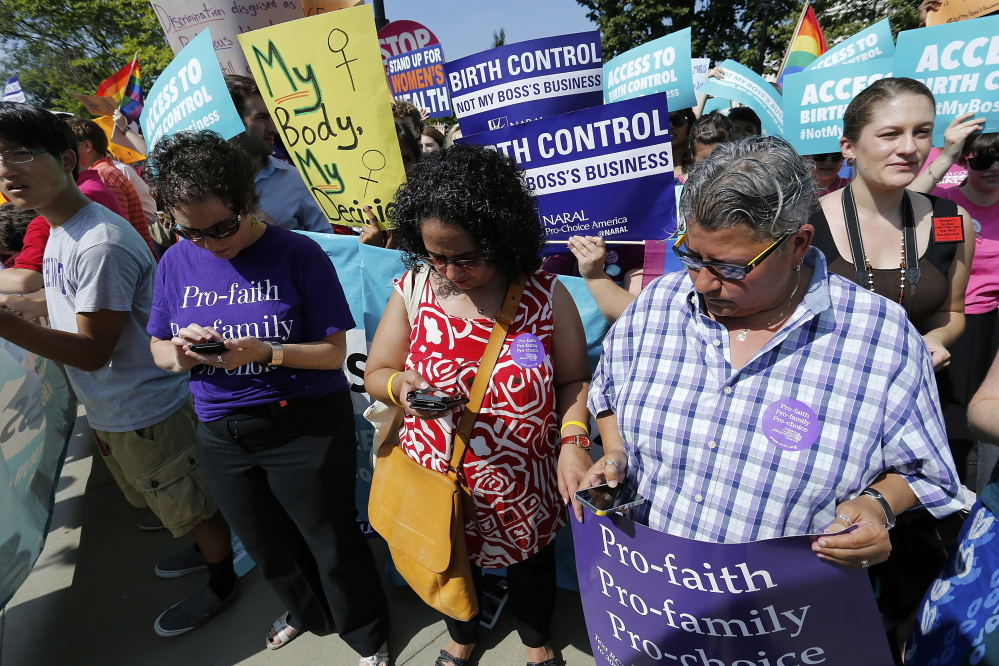 Demonstrators in support of abortion and contraceptive rights read on their mobile phones as the ruling for Hobby Lobby against their cause was announced outside the U.S. Supreme Court in Washington June 30, 2014. The U.S. Supreme Court on Monday ruled that business owners can object on religious grounds to a provision of U.S. President Barack Obama's healthcare law that requires closely held companies to provide health insurance that covers birth control. REUTERS/Jonathan Ernst (UNITED STATES - Tags: RELIGION POLITICS HEALTH CIVIL UNREST) - RTR3WGEF