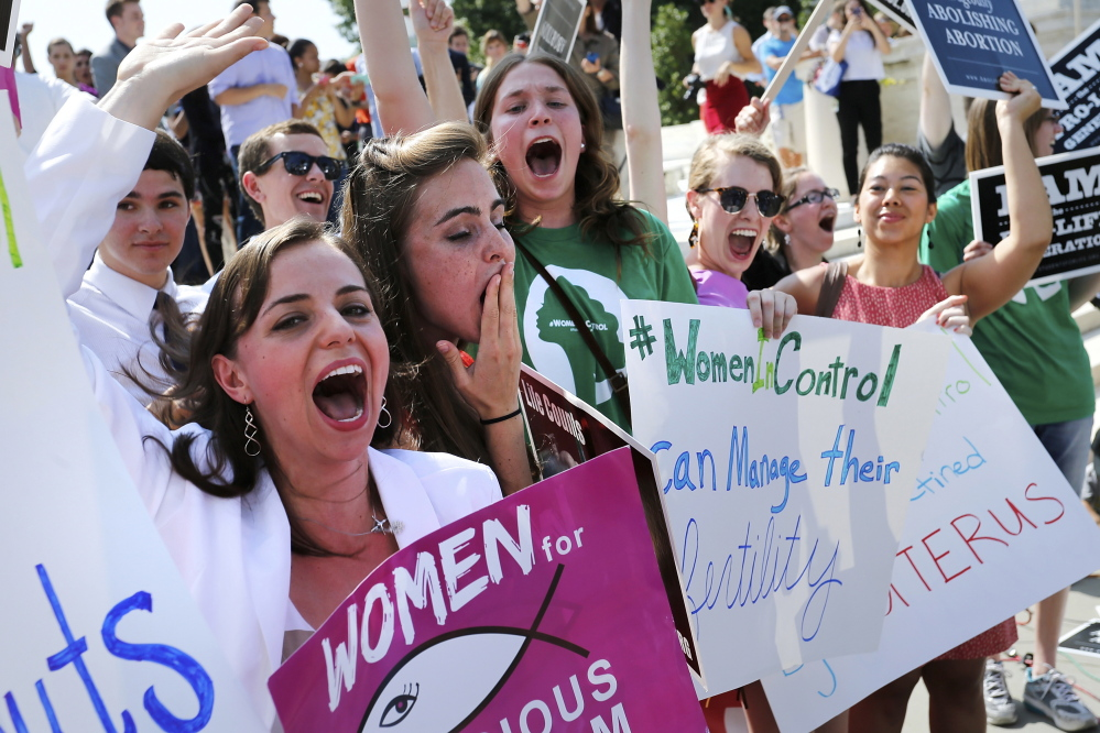 Anti-abortion demonstrators cheer as the ruling for Hobby Lobby was announced outside the U.S. Supreme Court in Washington June 30, 2014. The U.S. Supreme Court on Monday ruled that business owners can object on religious grounds to a provision of U.S. President Barack Obama's healthcare law that requires closely held private companies to provide health insurance that covers birth control. REUTERS/Jonathan Ernst (UNITED STATES - Tags: CIVIL UNREST RELIGION POLITICS HEALTH) - RTR3WH66