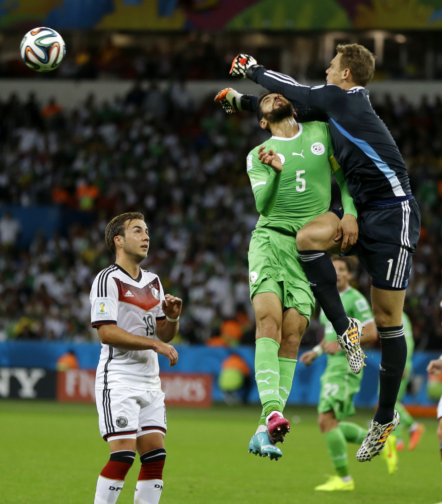 Germany's goalkeeper Manuel Neuer. right, punches the ball away from Algeria's Rafik Halliche during the World Cup round of 16 soccer match between Germany and Algeria.
