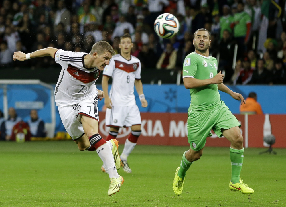 Germany's Bastian Schweinsteiger, left, heads the ball at the Algerian goal during the World Cup round of 16 soccer match between Germany and Algeria in Porto Alegre, Brazil, Monday, June 30, 2014.