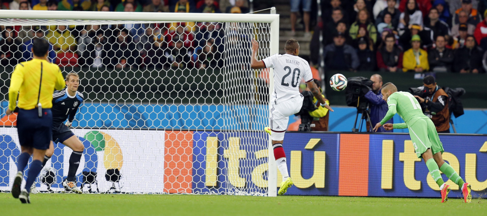 Algeria's Islam Slimani, right, scores a goal past Germany's goalkeeper Manuel Neuer which was disallowed during the World Cup round of 16 soccer match.