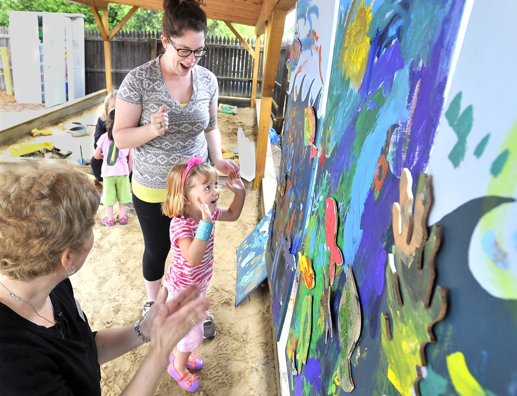 Evelyn Kirby, 3, expresses joy in her accomplishment of putting painted fish cutouts onto a painting of the ocean with speech-language pathologist Laurie Mack, left, of Northeast Hearing and Speech Center, and University of Southern Maine art education student Jacklyn Peters at Children's Odyssey, a pre-school in Portland on Thursday.