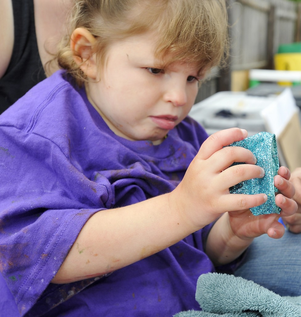 Tess Bigelow, 4, explores a wrist band made by art students from the University of Southern Maine to help young children explore textures and colors and use their dexterity  at Children's Odyssey pre-school in Portland on Thursday.