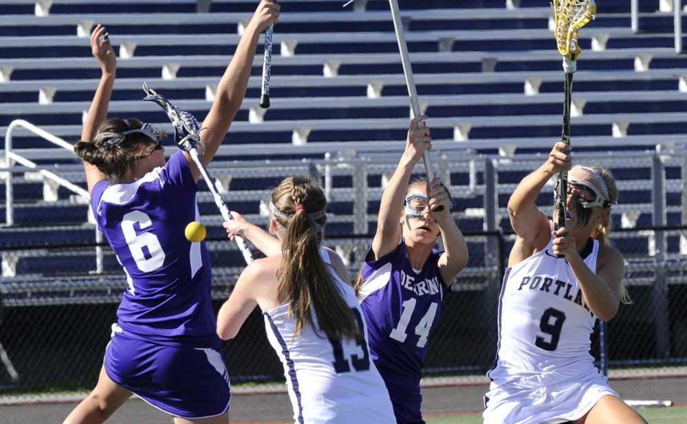 John Patriquin/Staff Photographer Emily Krabbe, left, and Micary Verville of Deering compete for the lacrosse ball with Merritt Ryan, 13, and Hallie Allex of Portland during Portland's 19-12 victory Tuesday at Fitzpatrick Stadium. The Bulldogs improved to 6-6 heading to the Eastern Class A tournament.