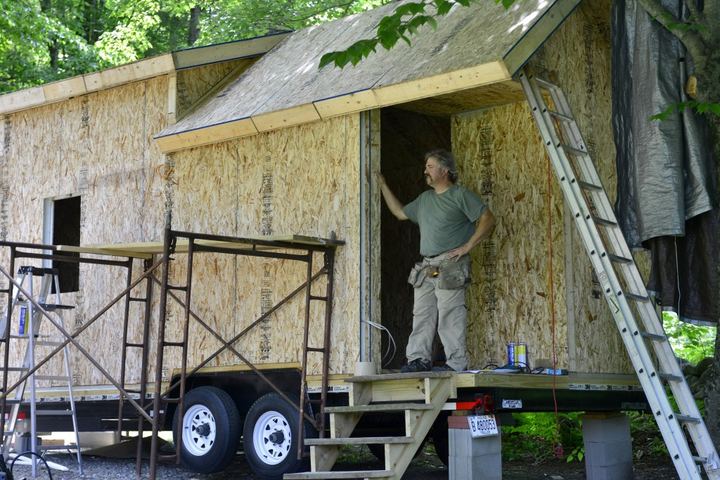 Alan Plummer works on his tiny house in his mother's driveway in Manchester. Plummer says he plans to start a tiny house community in rural Maine in the next few years. Logan Werlinger/Staff Photographer
