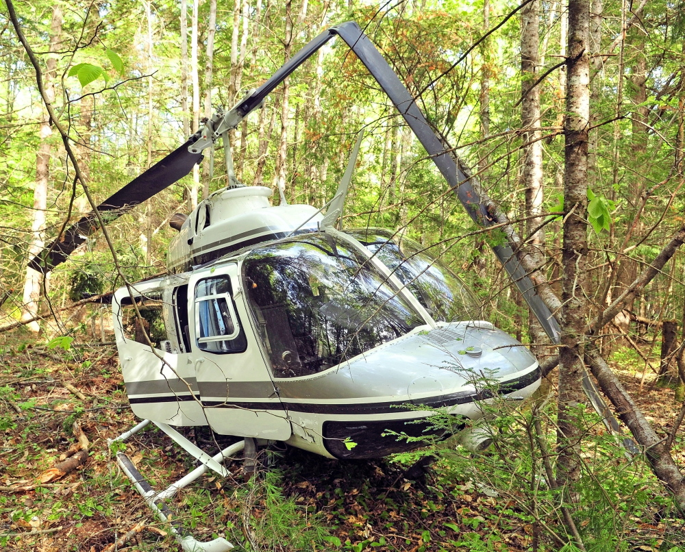 The helicopter crashed Friday in a heavily wooded area off East River Road in Whitefield. Maine Helicopters Inc., which owns the aircraft, is about a mile away to the south. Staff file photo by Joe Phelan
