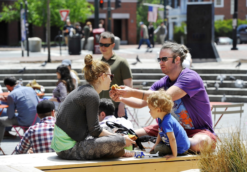 On a sun-soaked day in Congress Square Plaza in Portland, Michael Gatlin offers a bite of a sandwich to Bonnie Durham while their son, Ovid, 2, plays next to them. Gatlin and Durham said they plan to vote June 10 against the referendum making it harder to sell public spaces.