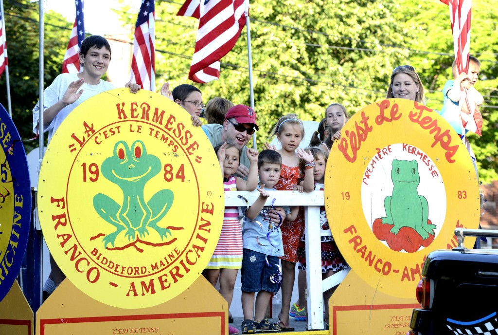 Kids on the La Kermesse float wave to the crowds during the La Kermesse parade along Alfred Street in Biddeford.