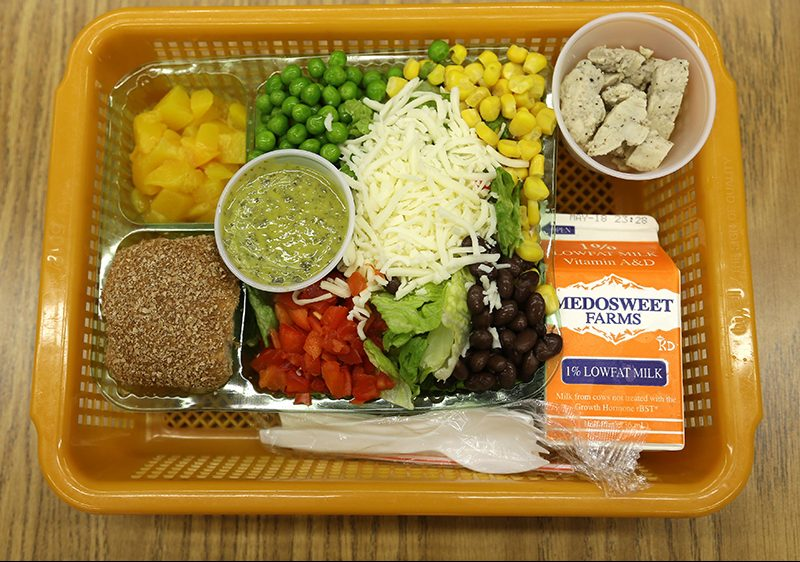 In this file photo, a school lunch salad entree option featuring low-sodium chicken, a whole-grain roll, fresh red peppers, and cilantro dressing is assembled in a lunch basket at Mirror Lake Elementary School in Federal Way, Wash., south of Seattle.