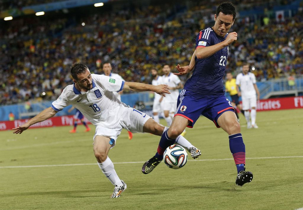 Greece's Giannis Fetfatzidis, left, challenges Japan's Maya Yoshida during the group C World Cup soccer match between Japan and Greece at the Arena das Dunas in Natal, Brazil, Thursday, June 19, 2014.