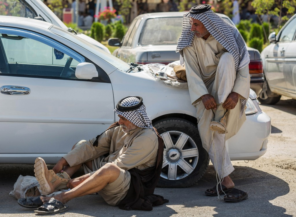 Members of an Iraqi volunteer force put on their newly issued boots in the Shiite holy city of Karbala, 50 miles (80 kilometers) south of Baghdad, Iraq, Tuesday, June 24, 2014.