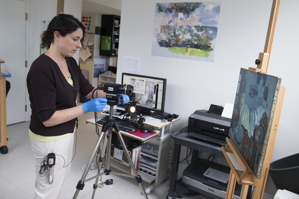 "Patricia Favero, associate conservator at The Phillips Collection, sets up an infared camera to view an image of a man found underneath one of Picasso's first masterpieces, ""The Blue Room,"" on June 10, 2014 in Washington. The Associated Press"