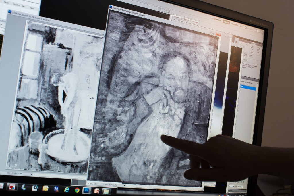"Patricia Favero, associate conservator at The Phillips Collection, points to an image of a man found underneath one of Picasso's first masterpieces, ""The Blue Room,"" on  June 10 in Washington.  The Associated Press"