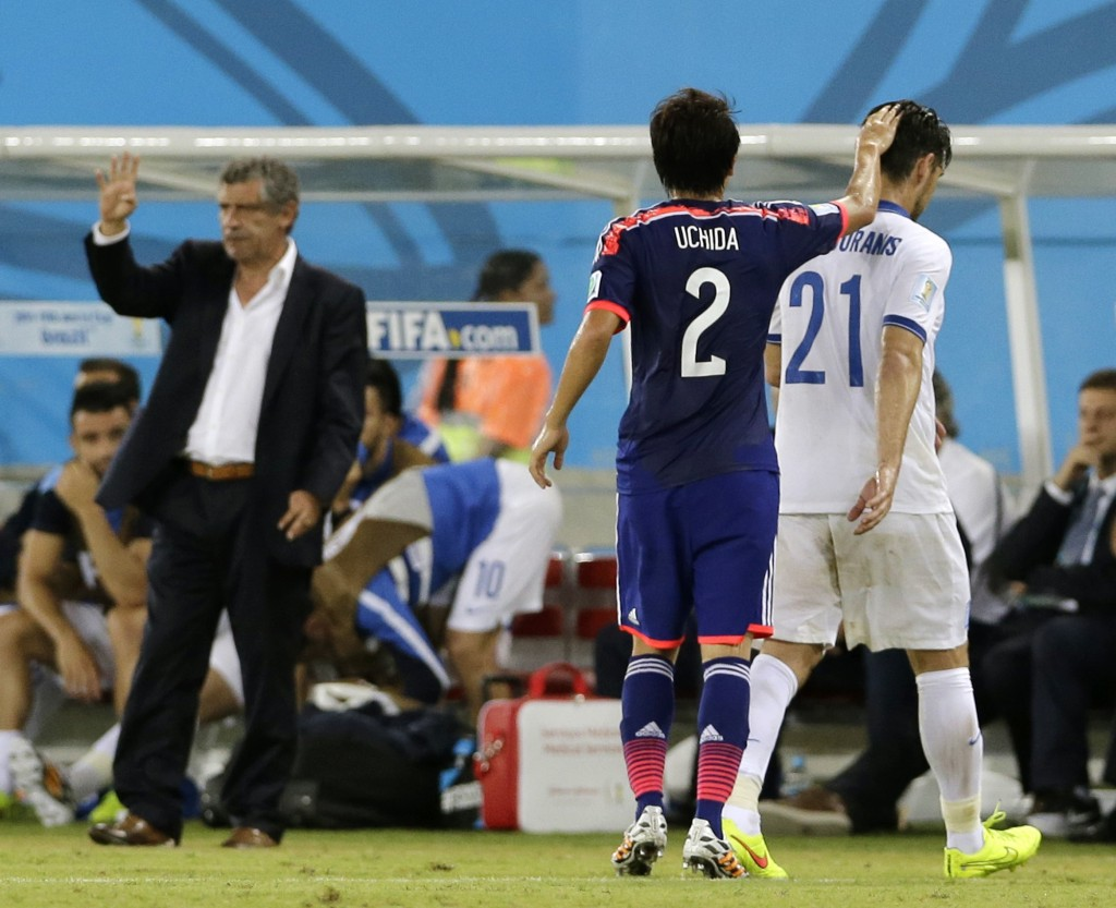 Japan's Atsuto Uchida (2) pats Greece's Kostas Katsouranis (21) on the head after Katsouranis was sent off by referee Joel Aguilar from El Salvador during the group C World Cup soccer match between Japan and Greece.