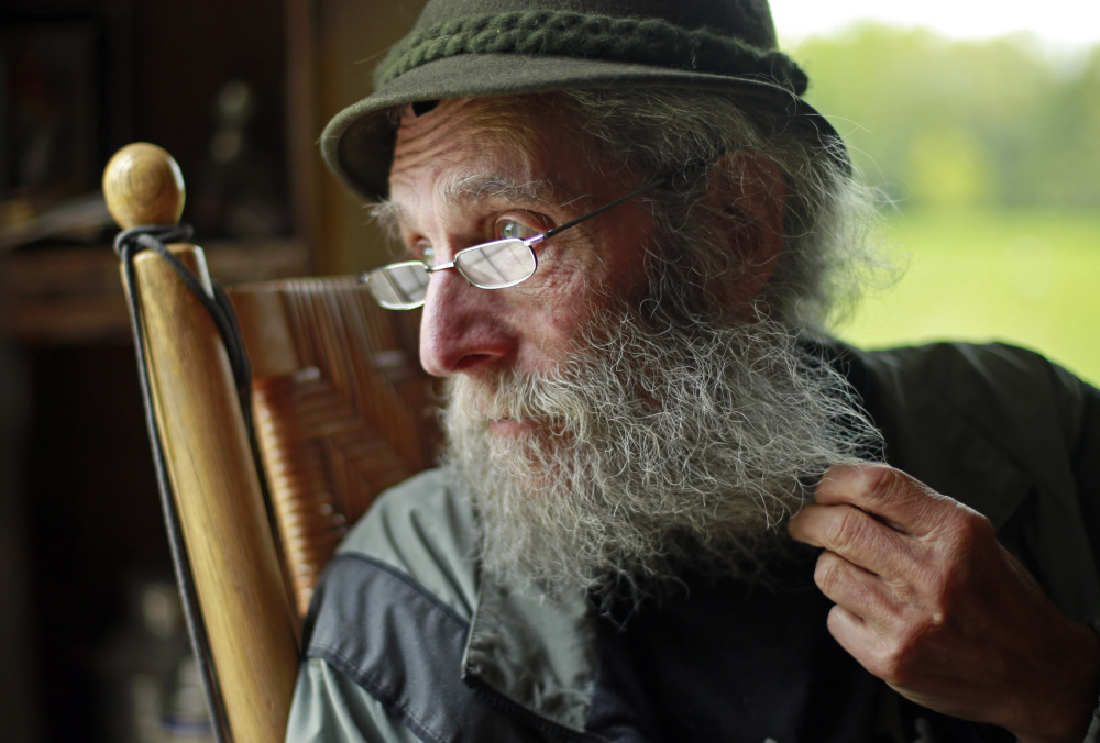 """Burt Shavitz pauses during an interview in May to watch a litter of fox kits play near his camp in Parkman. The reclusive beekeeper whose simple life became complicated by his status as a corporate icon is now the subject of a documentary, """"Burt's Buzz,"""" which opens Friday. The Associated Press/Robert F. Bukaty"""