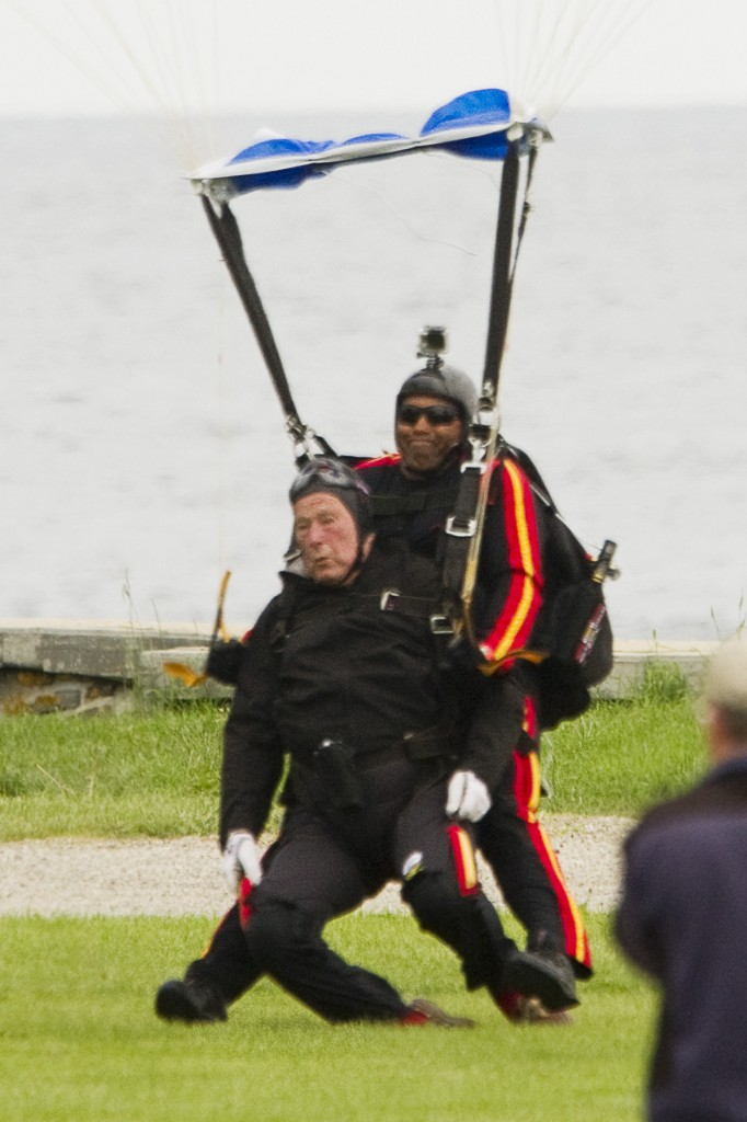 Former President George H. W. Bush lands on the ground at St. Anne's Church in Kennebunkport after a tandem skydive celebrating his 90th birthday on Thursday.