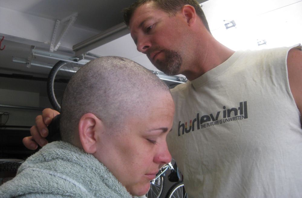Arrica Wallace has her head shaved by her husband, Matthew, in August 2012 in Manhattan, Kan. Arrica Wallace's cervical cancer did not respond to chemotherapy but she has completely clean scans after undergoing experimental immunotherapy. The Associated Press