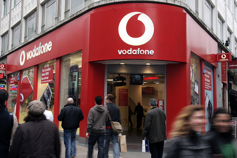 In this 2009 file photo, people walk by a Vodafone branch in central London. The Associated Press