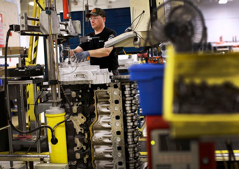 In this March 26, 2014 photo, Jerry Drury installs parts on a truck engine assembly line at Volvo Trucks' powertrain manufacturing facility in Hagerstown, Md.