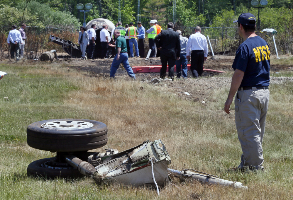 A National Transportation Safety Board official stands beside a piece of the landing gear at the scene Monday, June 2, 2014, in Bedford, Mass., where a plane plunged down an embankment and erupted in flames during a takeoff attempt at Hanscom Field on Saturday night. The Associated Press