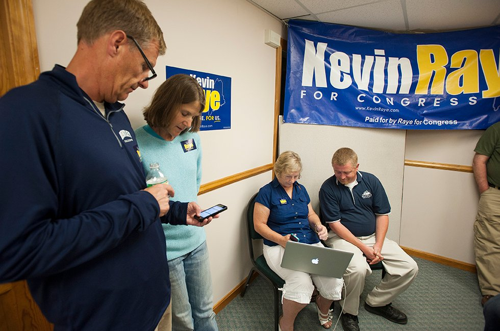 Doug and Nichi Farnham, left, of Bangor along with Dot Turner, center, and Chris Gardner, both of Washington County, check election results on their electronic devices as early election results come in for Kevin Raye at his campaign headquarters in Bangor on Tuesday. Kevin Bennett Photo