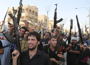 Shiite tribal fighters raise their weapons and chant slogans against the al-Qaida-inspired Islamic State of Iraq and the Levant (ISIL) in the northwest Baghdad's Shula neighborhood, Iraq, Monday. The Associated Press