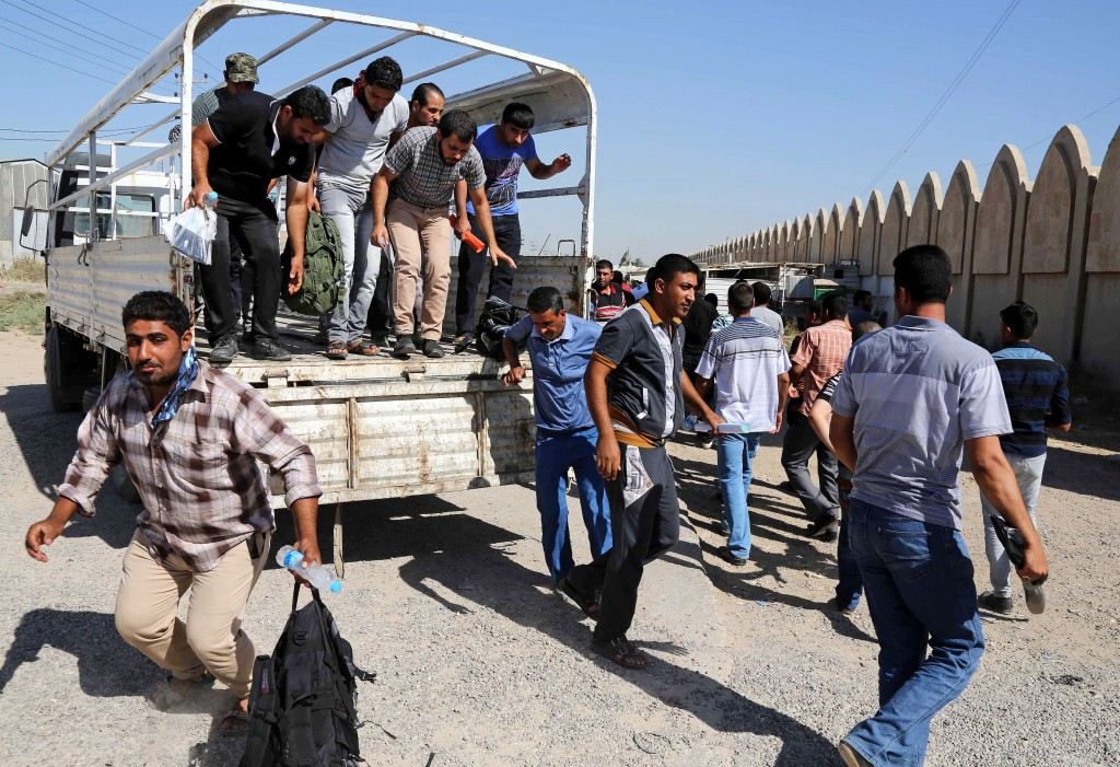 Iraqi men jump out of a truck at the main recruiting center as they volunteer for military service in Baghdad, Iraq, Tuesday, June 24, 2014, after authorities urged Iraqis to help battle insurgents.