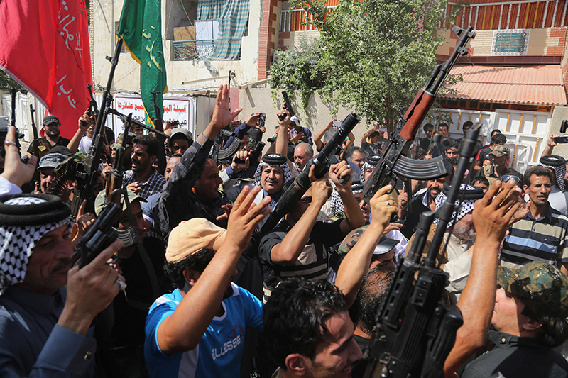 Iraqi Shiite tribal fighters raise their weapons and chant slogans against the al-Qaida inspired Islamic State of Iraq and the Levant (ISIL) in Baghdad's Sadr city, Iraq, Saturday.