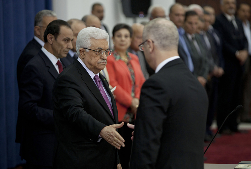 Palestinian Prime Minister Rami Hamdallah, right, extends his hand to shake hands with Palestinian President Mahmoud Abbas during a swearing-in ceremony of the unity government in the West Bank city of Ramallah on Monday. The Associated Press