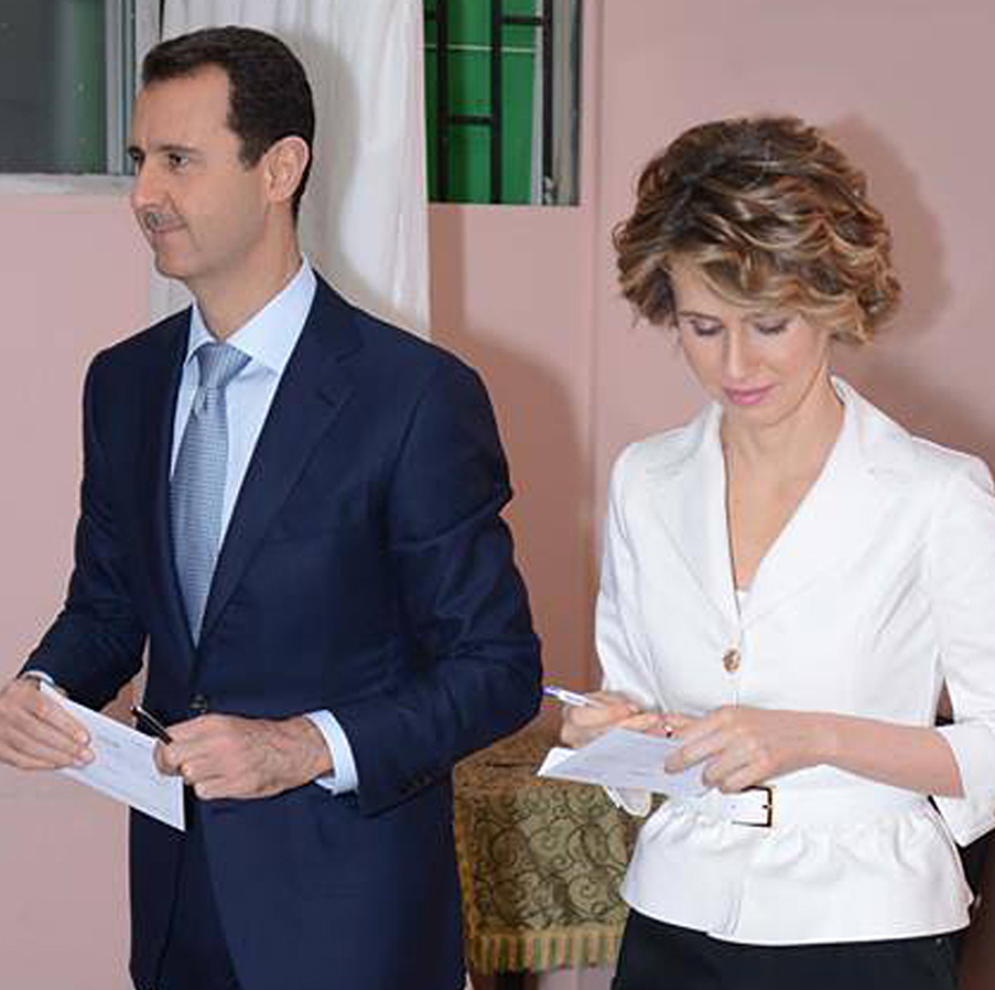 Syrian President Bashar Assad and first lady Asma Assad leave a voting booth in Damascus on Tuesday. The Associated Press