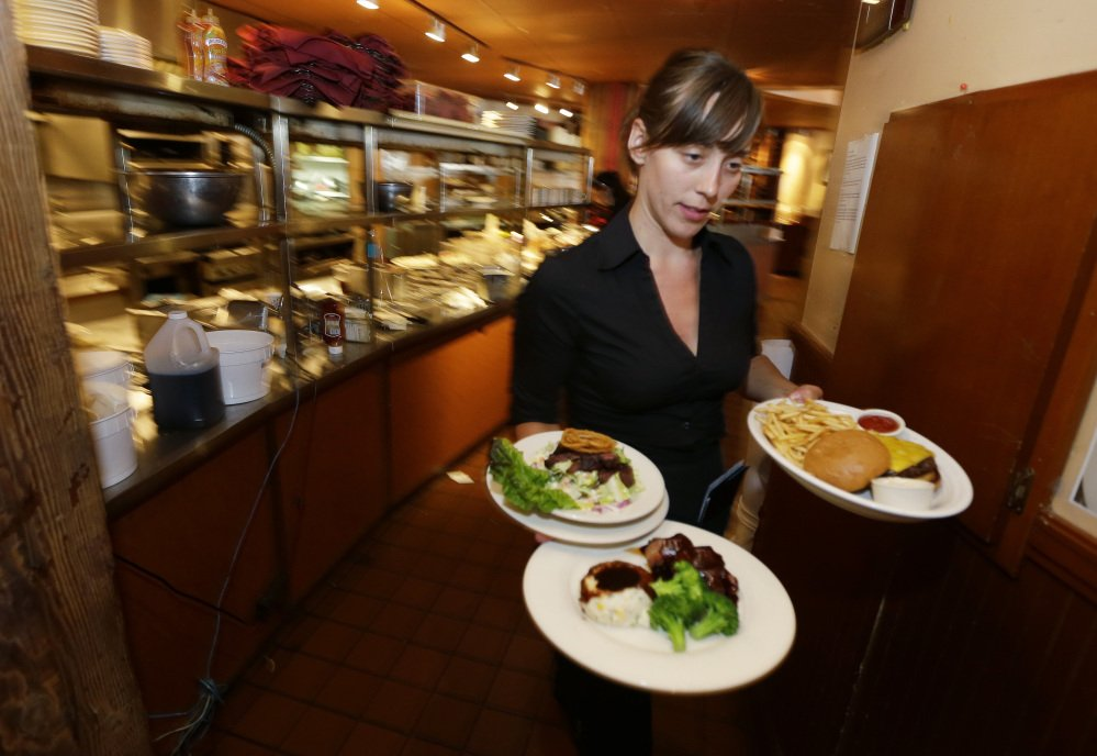 The Associated Press/Ted S. Warren In this June 2, 2014 photo, Wendy Harrison, a waitress at the icon Grill in Seattle, carries food to a table as she works during lunchtime. An Associated Press comparison of the cost of living at several other major U.S. cities found that a $15 minimum wage, like Seattle adopted this week, will make a difference, but won't buy a lavish lifestyle.