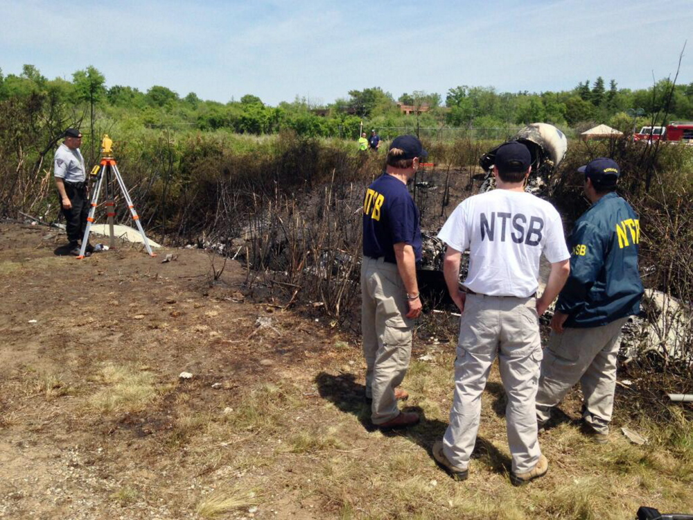 This photo provided by the National Transportation Safety Board, shows NTSB investigators at the scene of a plane that plunged down an embankment and erupted in flames during a takeoff attempt Saturday night at Hanscom Field in Bedford, Mass. The Associated Press