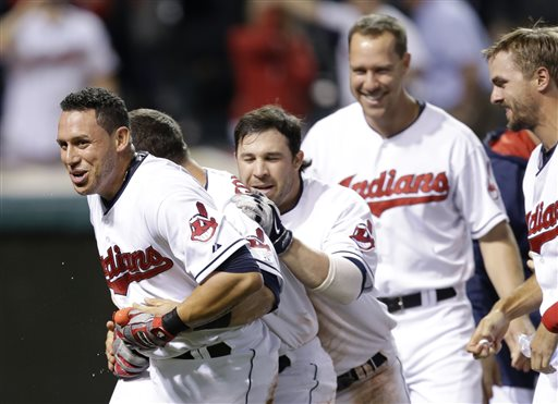 Teammates mob Indians shortstop Asdrubal Cabrera, front, after he hit a game-winning three-run home run off Red Sox relief pitcher Edward Mujica in the 12th inning Thursday in Cleveland. The Associated Press