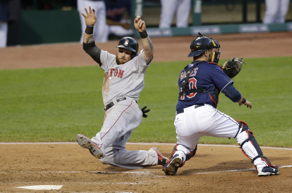 Boston Red Sox's Jonny Gomes, left, scores as Cleveland Indians catcher Yan Gomes waits for the ball in the sixth inning of a baseball game, Tuesday, June 3, 2014, in Cleveland. Gomes scored on a single by Jonathan Herrera. (AP Photo/Tony Dejak)