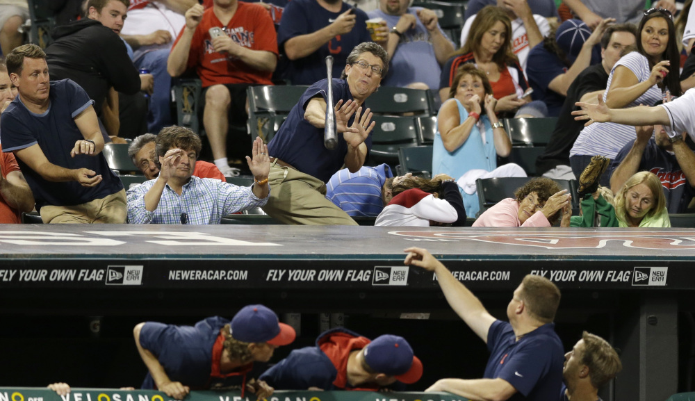 Fans try to dodge a bat that came loose from the hands of Cleveland Indians' Asdrubal Cabrera in the seventh inning of a baseball game against the Boston Red Sox, Tuesday, June 3, 2014, in Cleveland. (AP Photo/Tony Dejak)