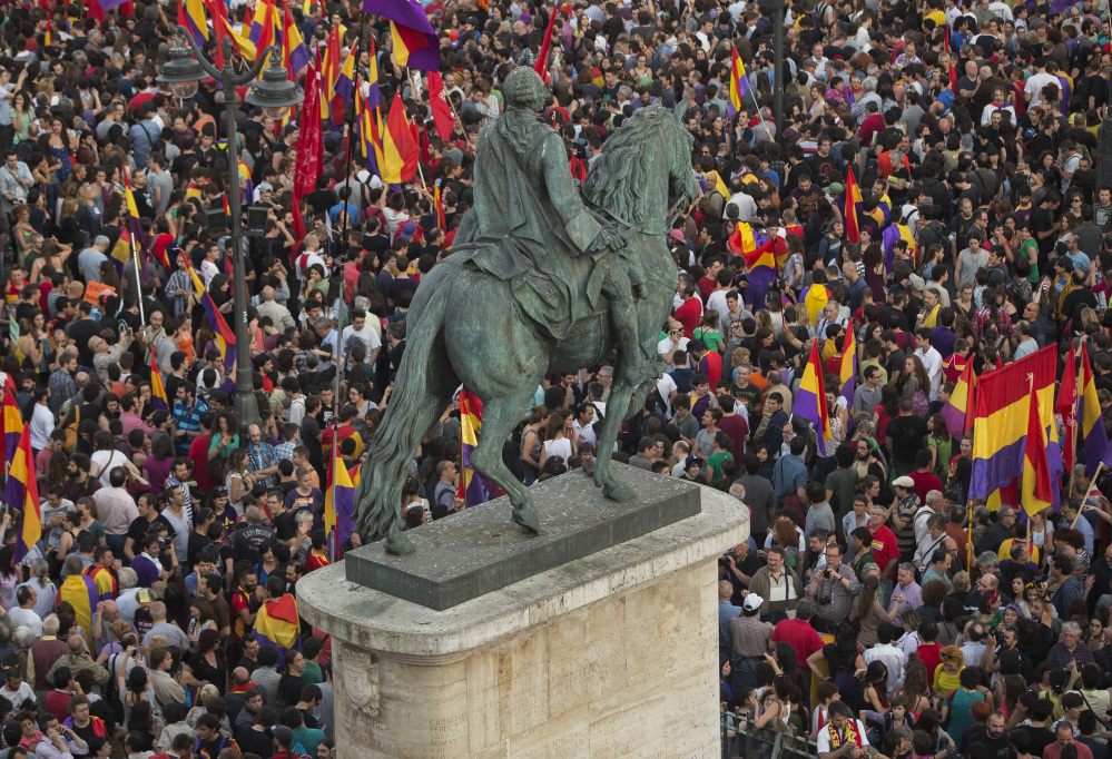 Crowds of people gather and wave republican flags around the monument of Charles III, King of Spain, in the main square of Madrid on Monday after the announcement of the planned abdication of Spain's King Juan Carlos. The Associated Press