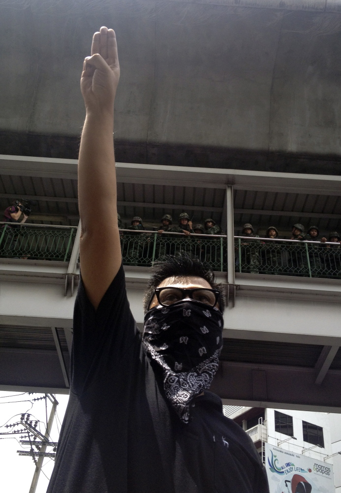 The Associated Press An anti-coup protester gives a three-finger salute as soldiers keep eyes on him from an elevated walkway near a rally site in central Bangkok on Sunday. Thailand's military rulers say they are monitoring the new form of silent resistance to the coup.