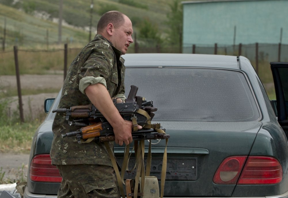 The Associated Press A pro-Russian rebel loads a car with weapons seized from a Ukrainian military unit in eastern Ukraine on Wednesday.
