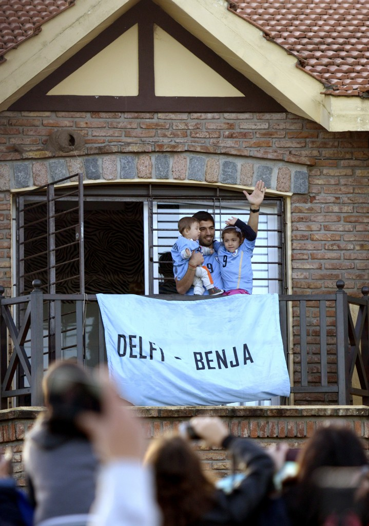 Uruguay's soccer player Luis Suarez, with his children Benjamin, left, and Delfina, waves to fans from his home, before the start of his team's World Cup round 16 match with Colombia, from which he was banned and Uruguay lost.